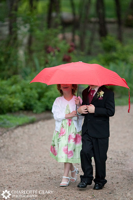 Ring bearer and flower girl under umbrella