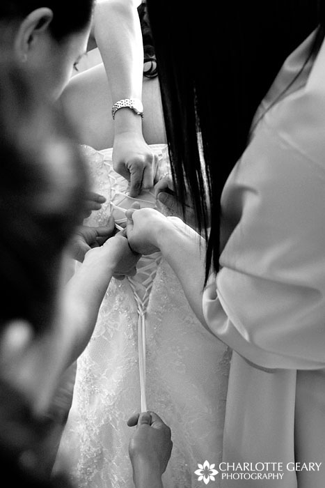 Bridesmaids lacing a corset gown