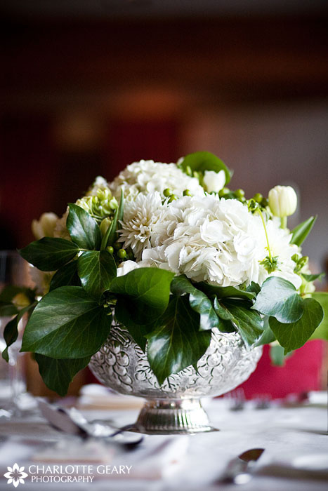 Green and white centerpiece in a silver vase